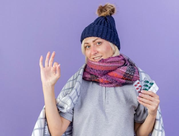 Lächelnde junge blonde kranke slawische frau, die wintermütze und schal trägt, die in karierte gesten ok handzeichen eingewickelt werden
