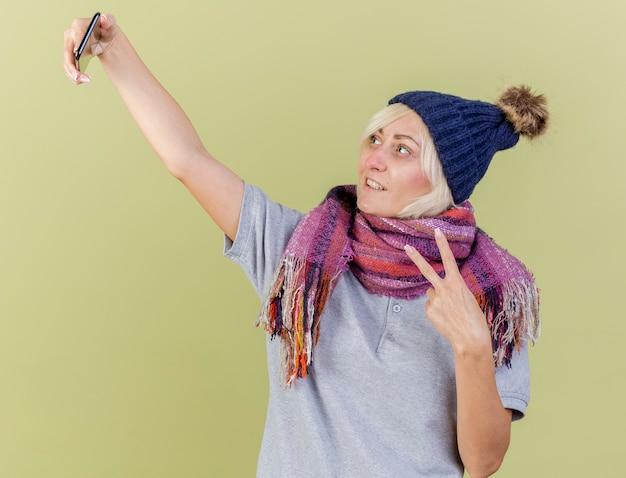 Lächelnde junge blonde kranke slawische frau, die wintermütze und schal trägt, gestikuliert siegeshandzeichen, das telefon lokalisiert auf olivgrüner wand mit kopienraum betrachtet