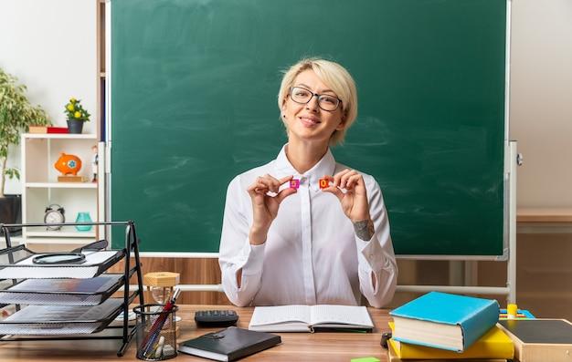 Lächelnde junge blonde lehrerin mit brille, die am schreibtisch mit schulmaterial im klassenzimmer sitzt und nach vorne schaut und kleine quadratische zahlen fünf und null zeigt