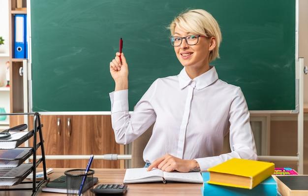 Lächelnde junge blonde lehrerin mit brille, die am schreibtisch mit schulwerkzeugen im klassenzimmer sitzt und mit dem finger auf den notizblock zeigt, der mit dem stift auf die tafel zeigt