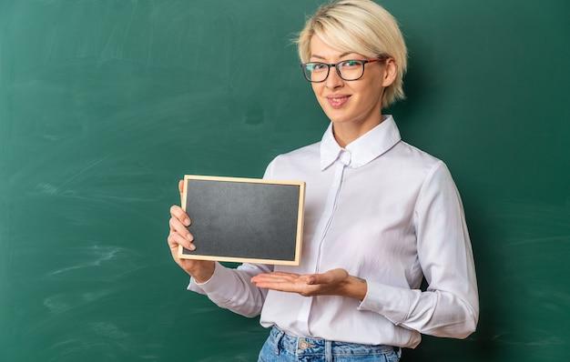 Lächelnde junge blonde lehrerin mit brille im klassenzimmer, die vor der tafel steht und eine mini-tafel zeigt, die nach vorne mit kopienraum schaut