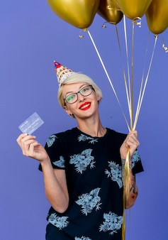 Lächelnde junge blonde partyfrau, die brille und geburtstagskappe hält, die luftballons und kreditkarte hält, die front lokalisiert auf lila wand betrachten