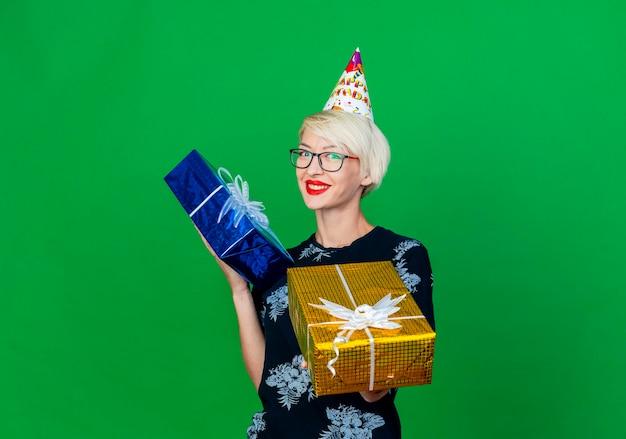 Lächelnde junge blonde partyfrau, die brille und geburtstagskappe hält und geschenkbox nach vorne streckt, betrachtet front lokalisiert auf grüner wand mit kopienraum