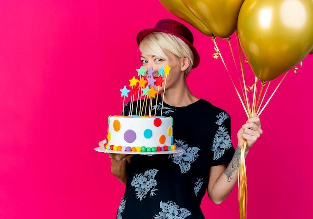 Lächelnde junge blonde partyfrau, die partyhut hält, der luftballons und geburtstagstorte mit sternen hält, die front lokalisiert auf rosa wand mit kopienraum betrachten