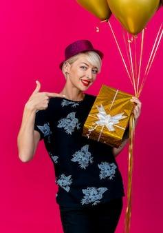 Lächelnde junge blonde partyfrau, die partyhut hält, der luftballons und geschenkbox hält, die auf geschenkbox zeigt, die vorne auf rosa wand lokalisiert betrachtet