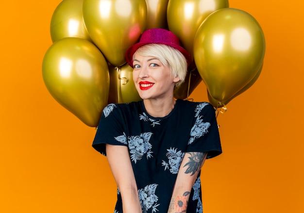 Lächelnde junge blonde partyfrau, die partyhut trägt, der vor ballons steht, die front lokalisiert auf orange wand betrachten