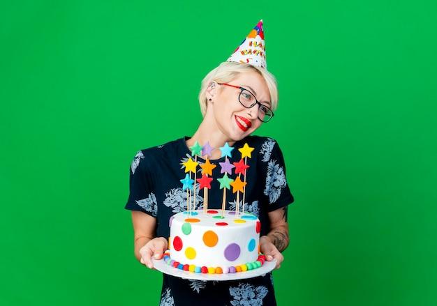 Lächelnde junge blonde partygirl, die brille und geburtstagskappe hält, die geburtstagstorte mit sternen hält, die seite lokalisiert auf grünem hintergrund mit kopienraum betrachten