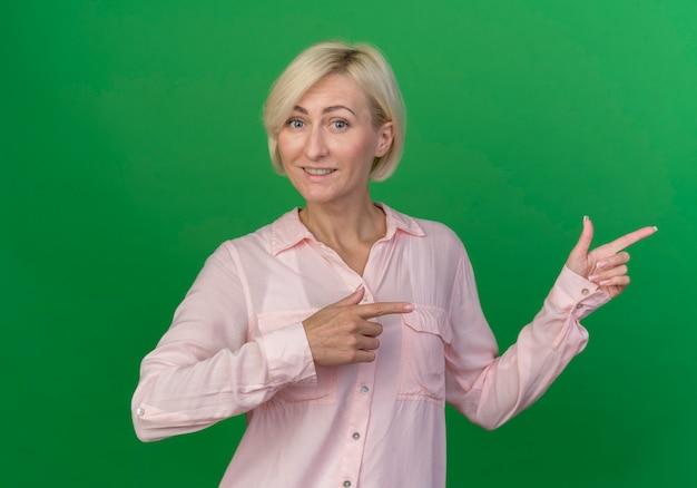 Lächelnde junge blonde slawische frau, die auf seite lokalisiert auf grünem hintergrund zeigt