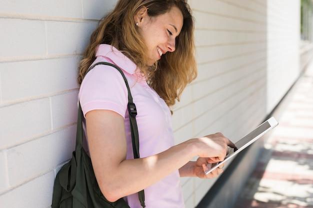 Lächelnde junge blondine, die tablette auf weißer wand verwendet