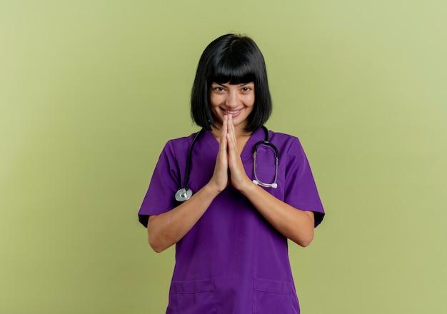 Lächelnde junge brünette ärztin in uniform mit stethoskop hält hände zusammen lokalisiert auf olivgrünem hintergrund mit kopienraum