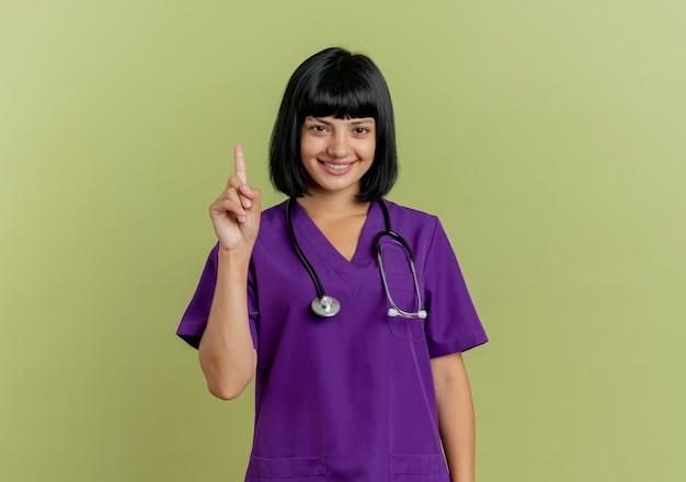 Lächelnde junge brünette ärztin in uniform mit stethoskop zeigt nach oben auf kamera lokalisiert auf olivgrünem hintergrund mit kopienraum