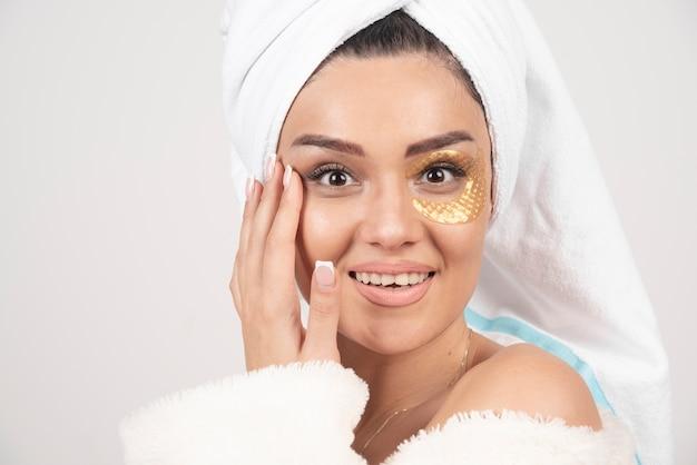 Lächelnde junge brünette frau, die bademantel mit kosmetischen augenklappen trägt