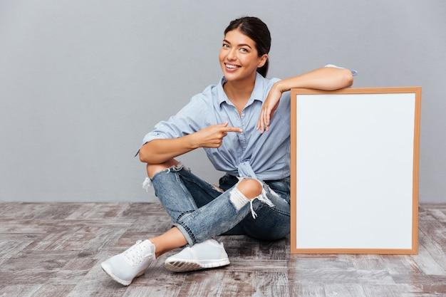 Lächelnde junge brünette frau, die mit dem finger auf ein leeres brett zeigt, während sie auf dem boden sitzt, isoliert auf einer grauen wand