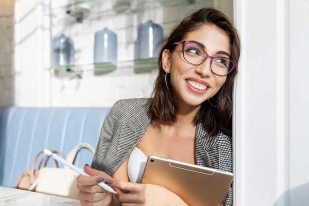 Lächelnde junge brünette frau in gläsern mit einer tablette sitzt in einem café und schaut aus dem fenster. online-business und fernunterricht.