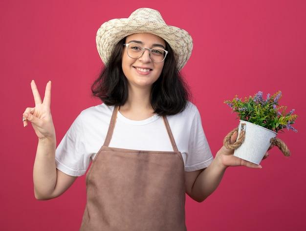 Lächelnde junge brünette weibliche gärtnerin in optischen gläsern und in uniform, die gartenhut trägt, hält blumentopf und gestikuliert siegeshandzeichen lokalisiert auf rosa wand mit kopienraum