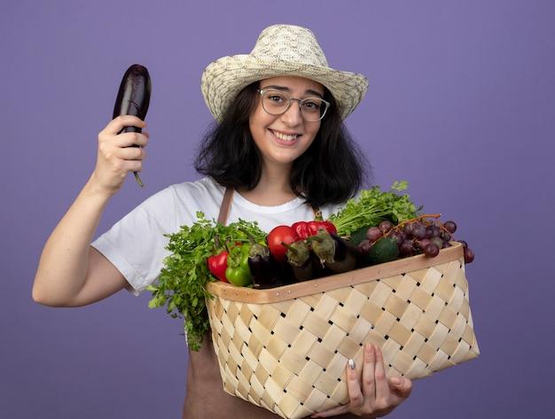 Lächelnde junge brünette weibliche gärtnerin in optischen gläsern und in uniform, die gartenhut trägt, hält gemüsekorb und aubergine lokalisiert auf lila wand
