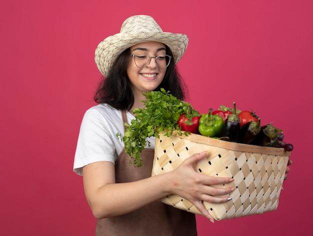 Lächelnde junge brünette weibliche gärtnerin in optischen gläsern und in uniform, die gartenhut trägt, hält und schaut auf gemüsekorb lokalisiert auf rosa wand