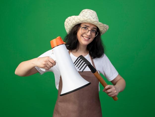 Lächelnde junge brünette weibliche gärtnerin in optischen gläsern und uniform, die gartenhut tragen, hält lautsprecher und rechen lokalisiert auf grüner wand