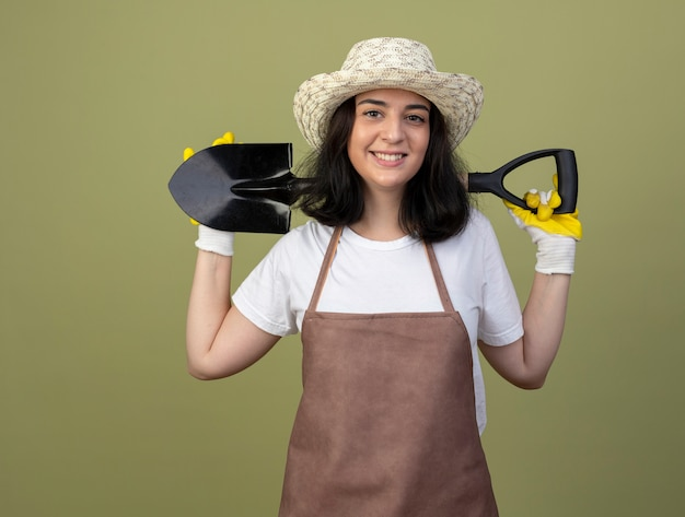 Lächelnde junge brünette weibliche gärtnerin in uniform, die gartenhut und handschuhe trägt, hält spaten hinter hals lokalisiert auf olivgrüner wand