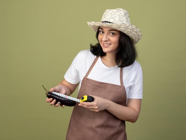Lächelnde junge brünette weibliche gärtnerin in uniform mit gartenhut, die auberginen mit maßband misst, isoliert auf olivgrüner wand