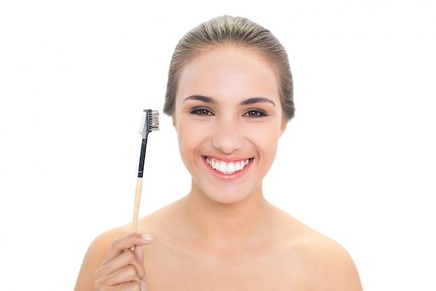 Lächelnde junge brunettefrau, die augenbrauenbürste hält