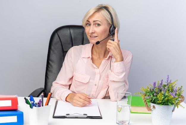 Lächelnde junge callcenter-betreiberin mit headset, die mit bürowerkzeugen am tisch sitzt