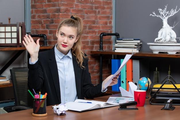 Lächelnde junge dame, die an einem tisch sitzt und das dokument im büro hält