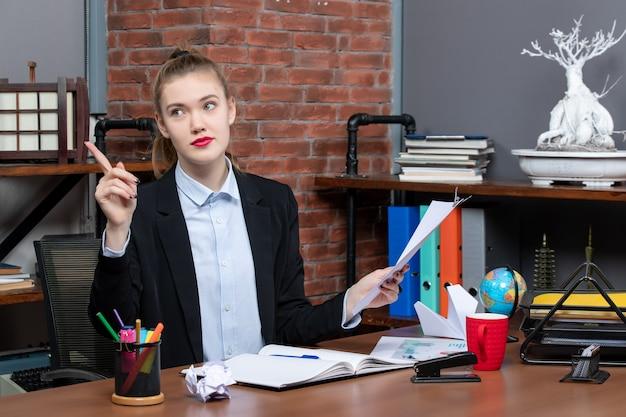 Lächelnde junge dame, die an einem tisch sitzt und das dokument im büro nach oben zeigt