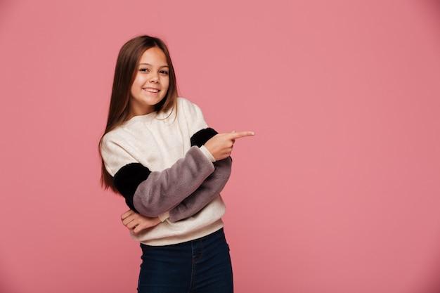 Lächelnde junge dame, die auf kopienraum und -c $ schauen zeigt