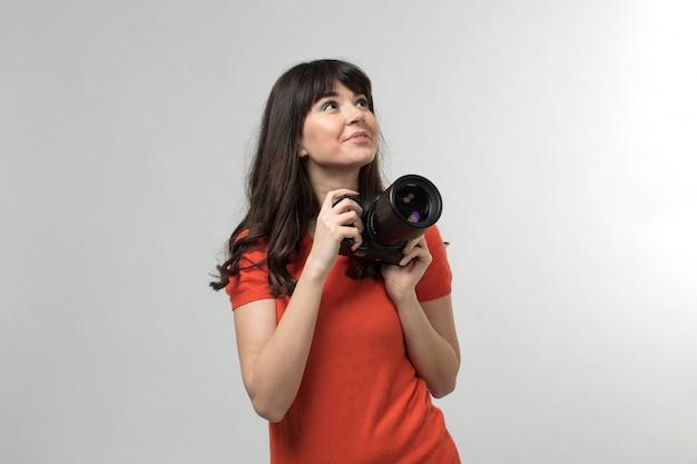 Lächelnde junge dame, die fotokamera in entworfenem t-shirt in guter laune mit langen haaren auf weiß hält