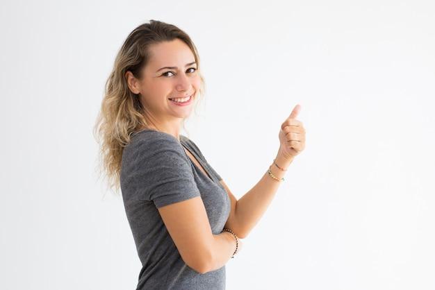 Lächelnde junge dame, die sich daumen zeigt und kamera betrachtet