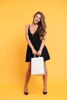 Lächelnde junge dame im schwarzen kleid, das einkaufstaschen hält.