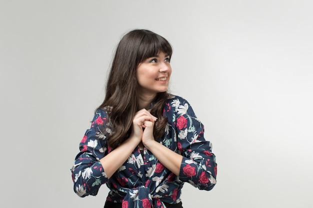 Lächelnde junge dame in entworfenem t-shirt in guter laune mit langen haaren auf weiß