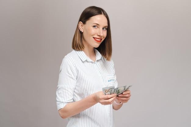 Lächelnde junge dame in gestreiftem hemd, die geld hält und zu ihnen über die graue wand schaut, die nach vorne schaut