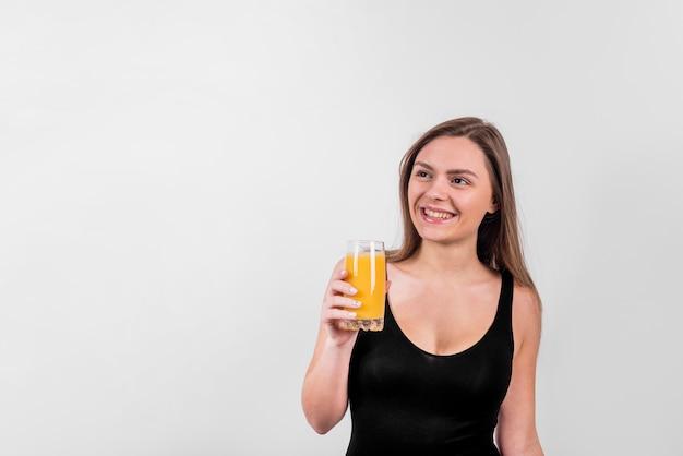Lächelnde junge dame mit einem glas saft