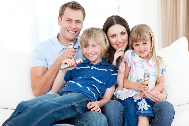 Lächelnde junge familie, die zusammen ein karaoke singt