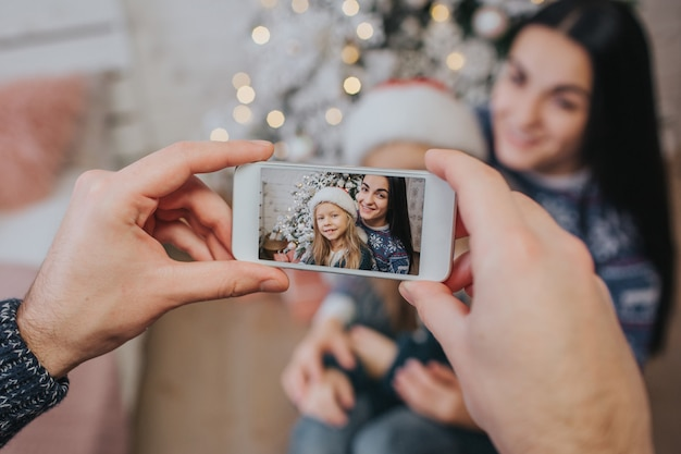 Lächelnde junge familie in der weihnachtsatmosphäre, die foto mit smartphone macht.