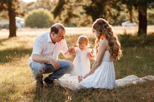 Lächelnde junge familie mit dem kleinen mädchen, das zeit zusammen im park verbringt und spazieren geht