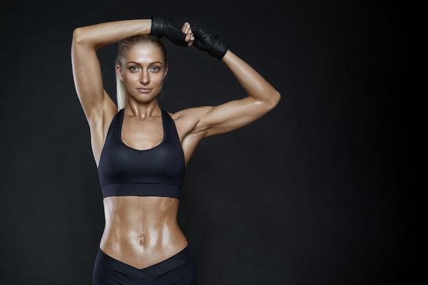 Lächelnde junge frau der fitness mit einem gesunden durchtrainierten körper