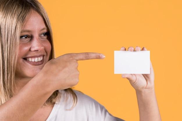 Lächelnde junge frau der unfähigkeit, die über unbelegte visitenkarte zeigt