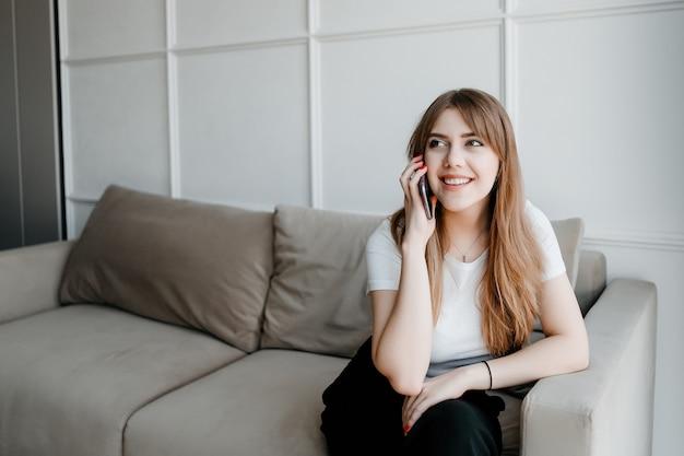 Lächelnde junge frau, die am telefon spricht, das auf einer couch zu hause sitzt