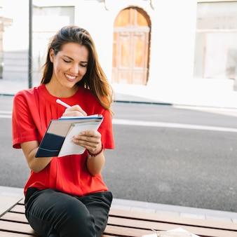 Lächelnde junge frau, die auf bankschreibensanmerkung im tagebuch sitzt