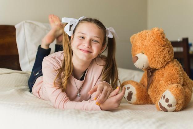 Lächelnde junge frau, die auf bett mit teddybären liegt