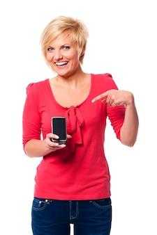Lächelnde junge frau, die auf bildschirm des handys zeigt