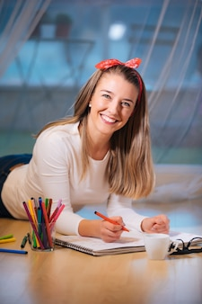 Lächelnde junge frau, die auf dem boden liegt und mit farbigen markern zeichnet