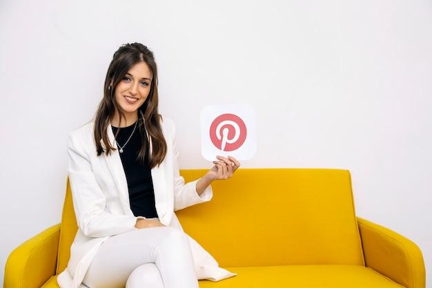 Lächelnde junge frau, die auf dem gelben sofa zeigt pinterest ikone sitzt