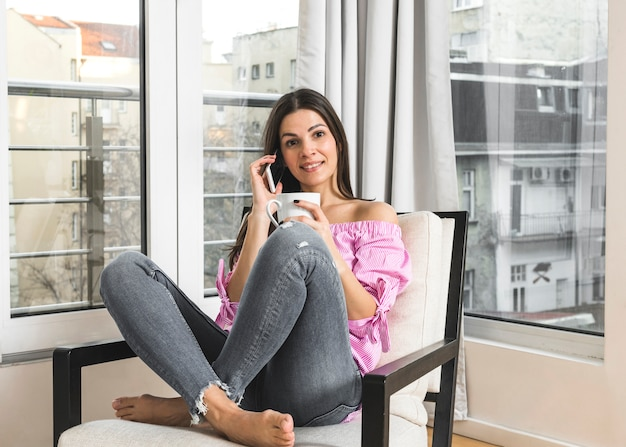 Lächelnde junge frau, die auf dem stuhl spricht am handy hält kaffeetasse in der hand sitzt