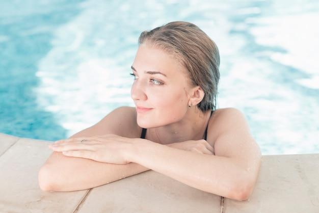 Lächelnde junge frau, die auf dem swimmingpoolrand sich lehnt