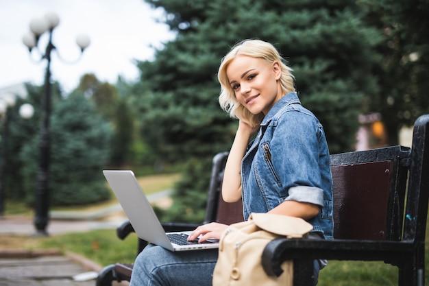 Lächelnde junge frau, die auf der bank sitzt und telefon und laptop im herbstmorgen der stadt benutzt