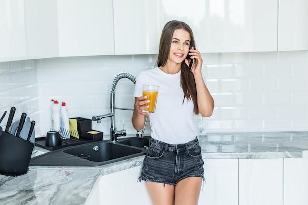 Lächelnde junge frau, die auf handy spricht, während sie auf einer küche mit glas saft steht